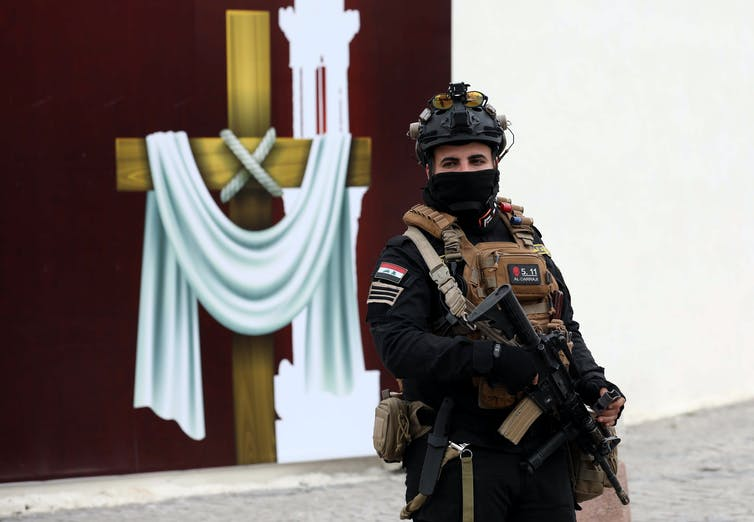 A soldier holding a rifle stands guard over a church in Baghdad. In the background is a cross decorated with a white robe.
