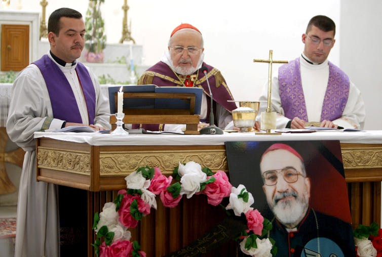 Three priests celebrate funeral mass in church in Baghdad. In front of altar is photograph of murdered archbishop Paulos Faraj Rahho.