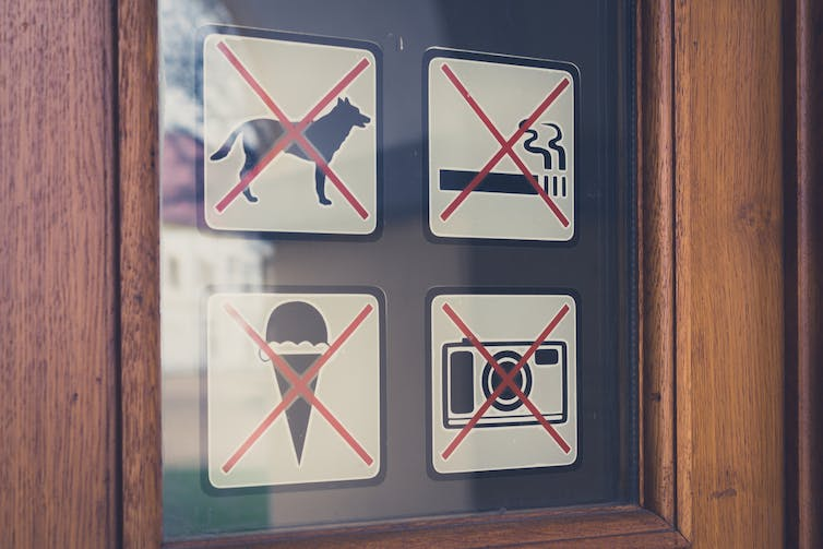 Sign on a door refusing dogs entry.