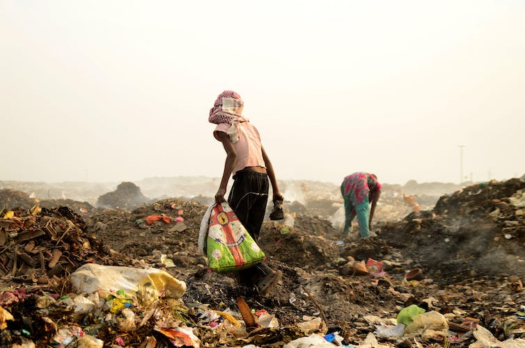 Two people pick through refuse at a huge dump site.