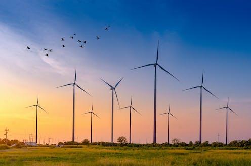 Wind turbines on land, colourful sky