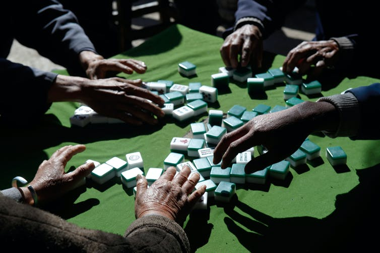 A majong game underway but only players' hands can be seen.
