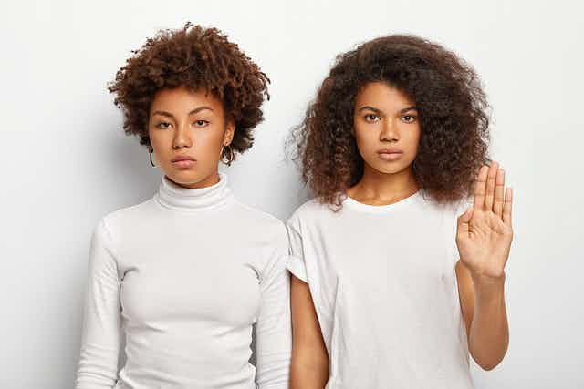 Two girls standing, one had her hand up in a stop gesture