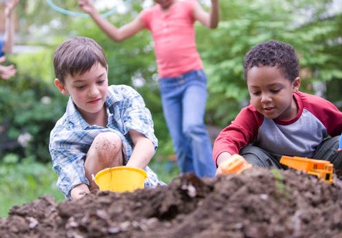 Two children playing with toys in a pile of dirt while two other kids play in the background