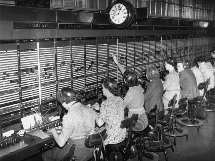 seated operators in front of telephone switchboard