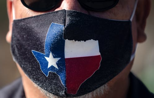 A man wears a face mask with the state of Texas on it