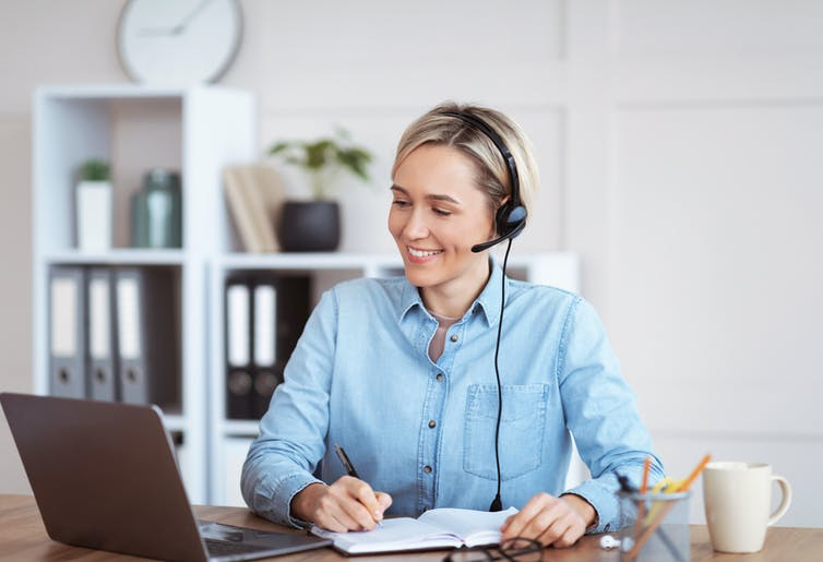 smiling women takes notes as she chats with colleagues online