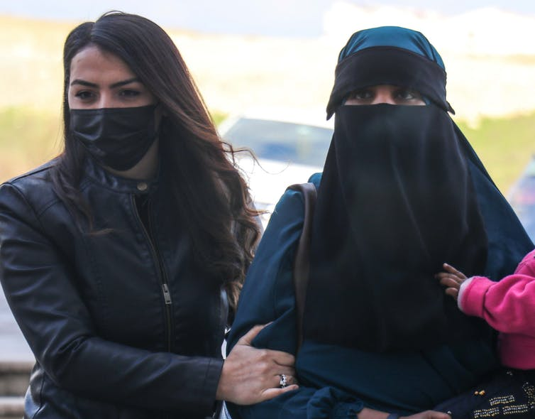Police woman in mask holding arm of woman with face covered