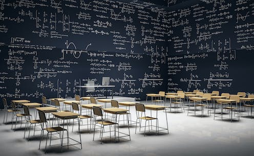 Study desks in a room with mathematical equations on the walls