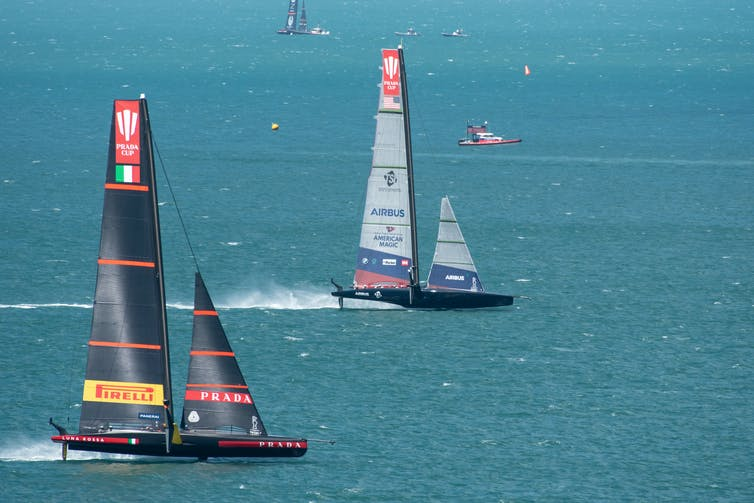 The two yacht at speed race across the harbour route.