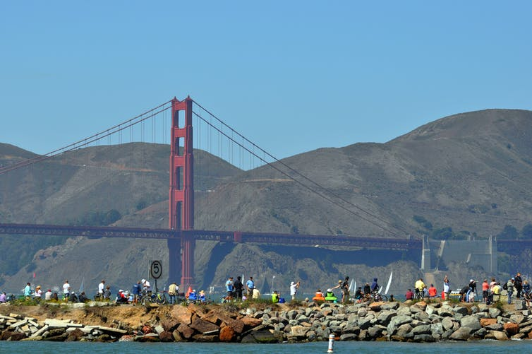 People lined up on the water's edge with the Golden Gate Bridge in the background.