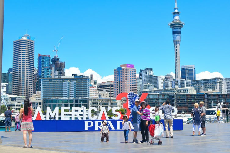 People taking photos at America's Cup sign on Auckland's waterfront.