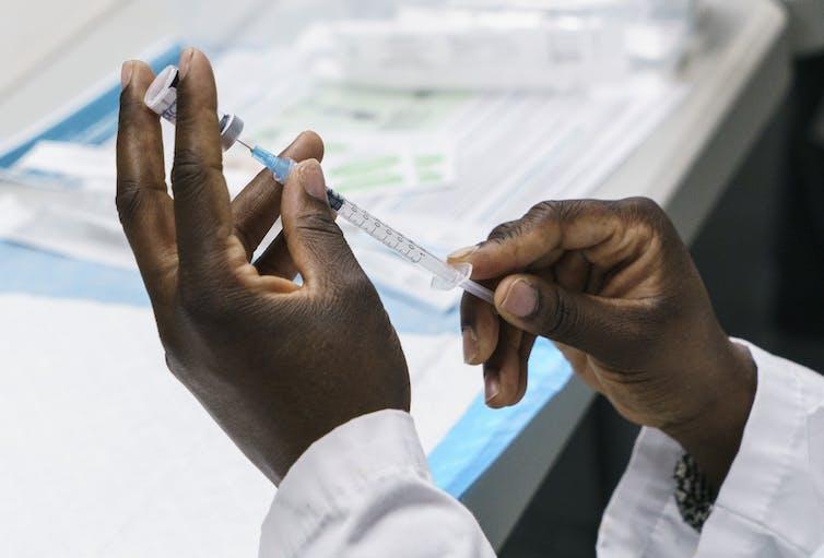 Hands preparing a syringe