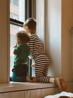 Two children on a windowsill looking outside at a tall building.