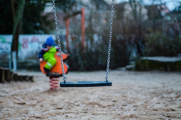 An empty swing in an empty playground
