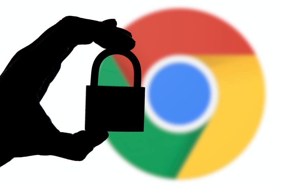 A hand holding a padlock in front of the Google Chrome icon