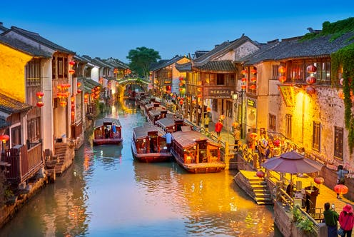 Shantang canal in Suzhou, eastern China, showing shops and boats plying their trade.ver in the city centre.