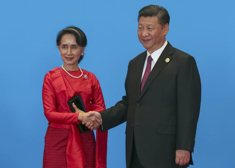 Aung San Suu Kyi shakes hands with Xi Jinping against a blue background.