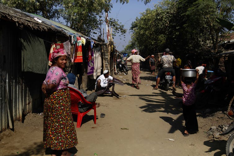 Rohingya people sit and walk by a temporary building.