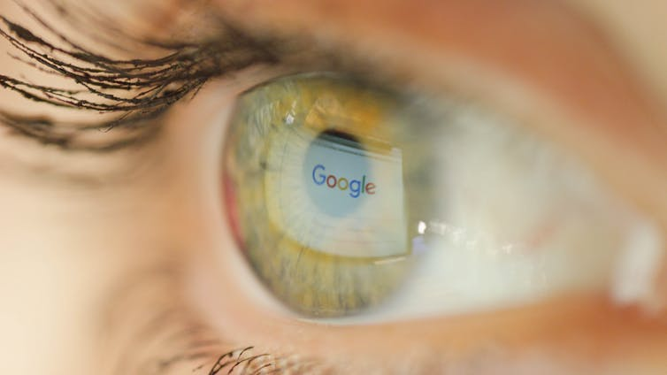 An eye reflects the Google logo