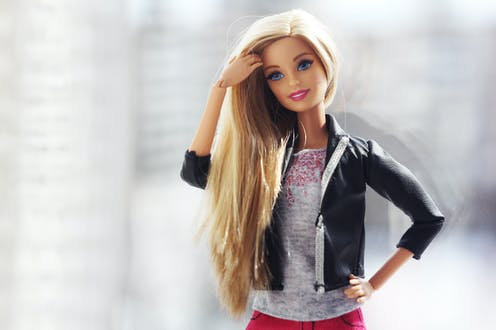 A barbie doll with blonde hair and her hand on her hip.