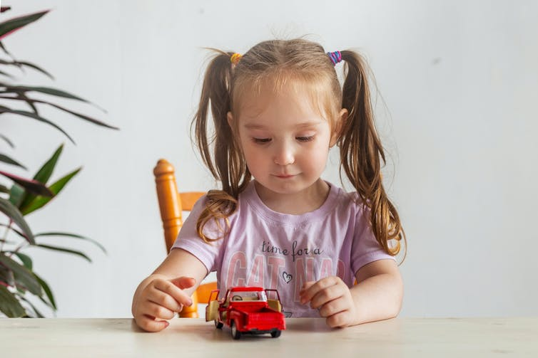 A girl playing with a red toy car.