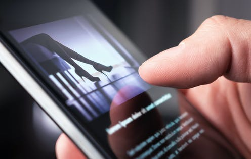A man looks at a photo of a woman in high heels on his phone.