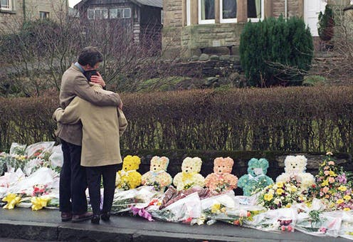 People visit flowers laid for the victims of the Dunblane shooting.