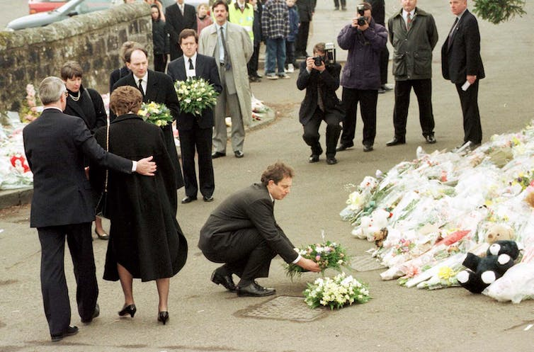 Tony Blair placing a wreath in front of a large pile of flowers with other mourners and photographers.
