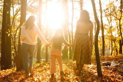 Dos mujeres pasean con una niña de la mano por un bosque otoñal.