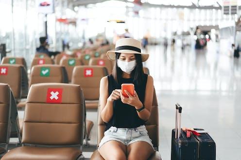 Una mujer con mascarilla en un aeropuerto junto a asientos anulados por la pandemia.