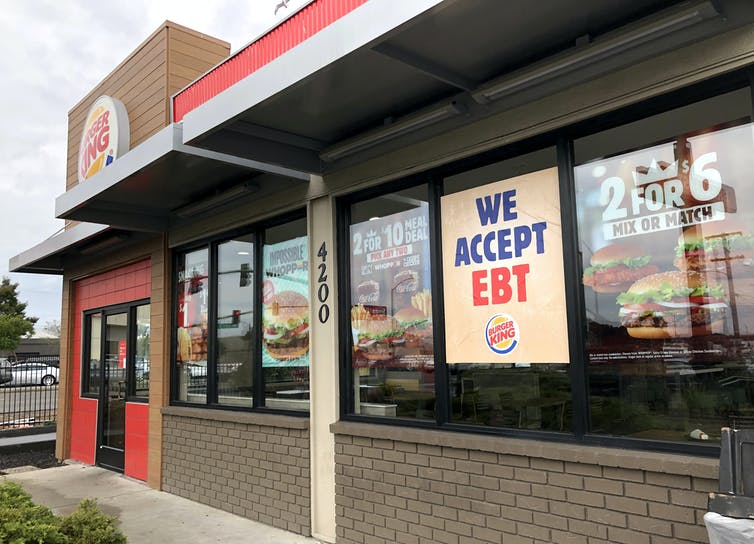 A Burger King outlet displaying a 'We Accept EBT' poster in the window.