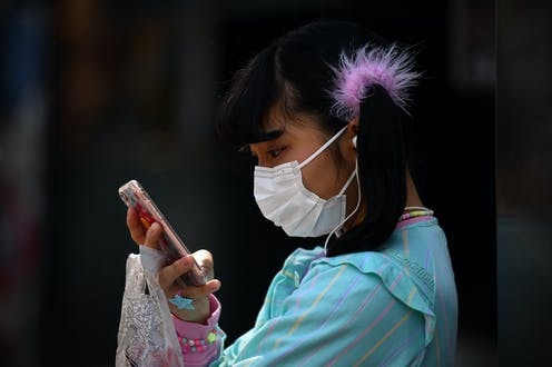 Girl wearing face mask holds mobile phone close to face