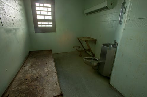 Interior of solitary confinement cell with metal bed, desk and toilet in an old prison