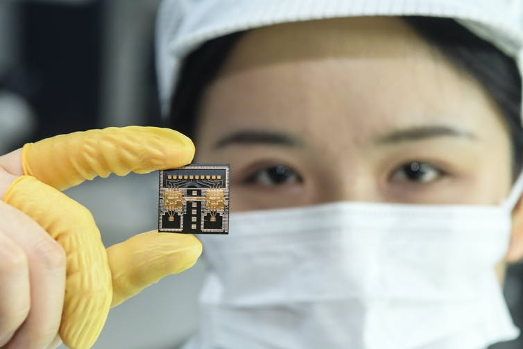 a worker wearing a facemask and finger gloves holds a semiconductor chip