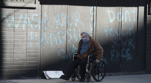 A man wearing a face mask wheels his wheelchair past a spray-painted wall that reads Wash Your Hands Don't Touch Your Face.