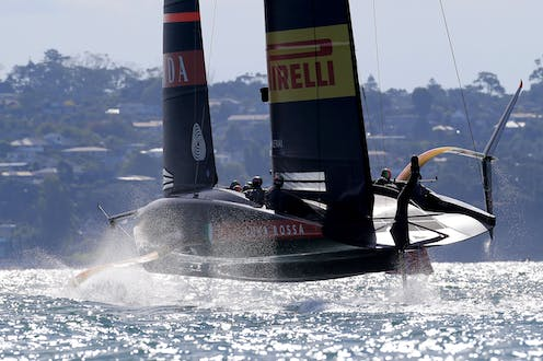 America's Cup yacht foiling with land and houses in background