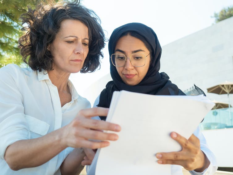 Two women read a document