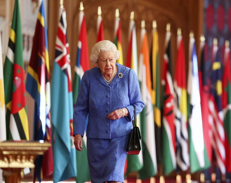 The Queen walking past Commonwealth flags at Windsor Castle.