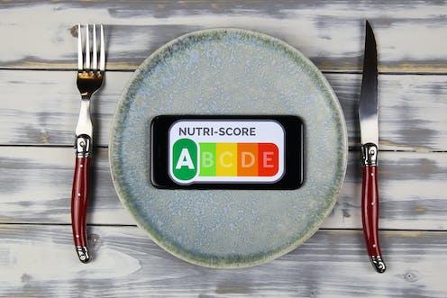 Plato con etiqueta de clasificación nutricional NutriScore falnqueado por cuchillo y tenedor.