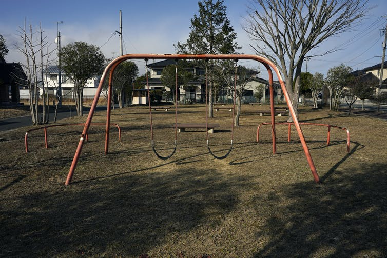 A red swing set stands alone in a vacant neighbourhood park.