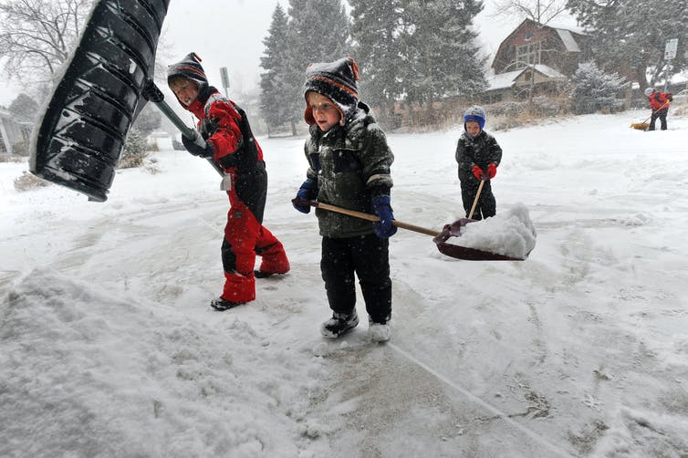 Young children shovel snow
