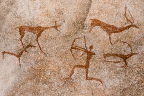 Cave drawing of an archer shooting at animals