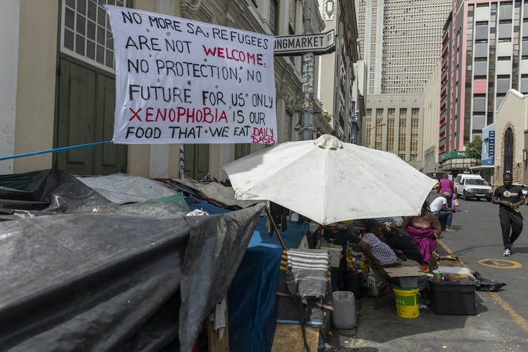 Sign written in black and red with text that reads: 'No more SA, refugees are not welcome. No protection, no future for us only xenophobia is our food that we eat daily basis', next to parasol covering refugee shelter