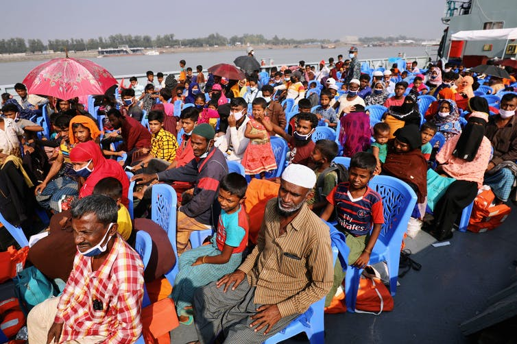 Rohingya refugees sit on a crowded ship