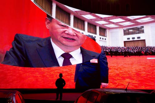 A child stands near a large screen showing photos of Chinese President Xi Jinping.