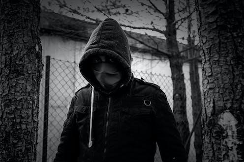 Fotografía en blanco y negro de un hombre encapuchado y con mascarilla que mira a cámara.