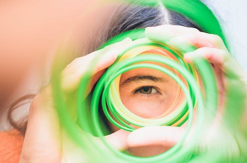 A young woman's eye seen through her hands holding a colored spiral