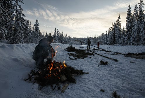 A person crouches near a fire in the snow near a road and surrounded by tall trees