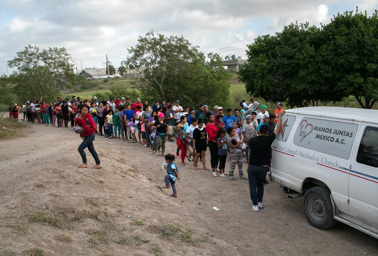 Line of people standing behind a van, with children playing in dirt in foreground